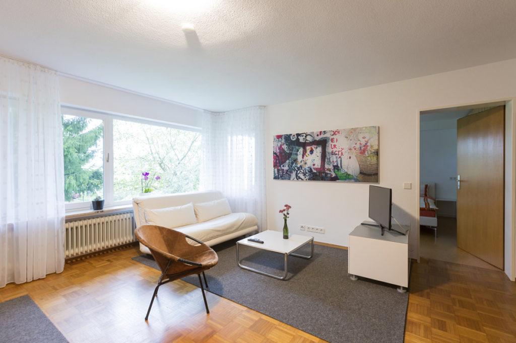 Gemütliches Wohnzimmer mit Fernseher und schönem Ausblick