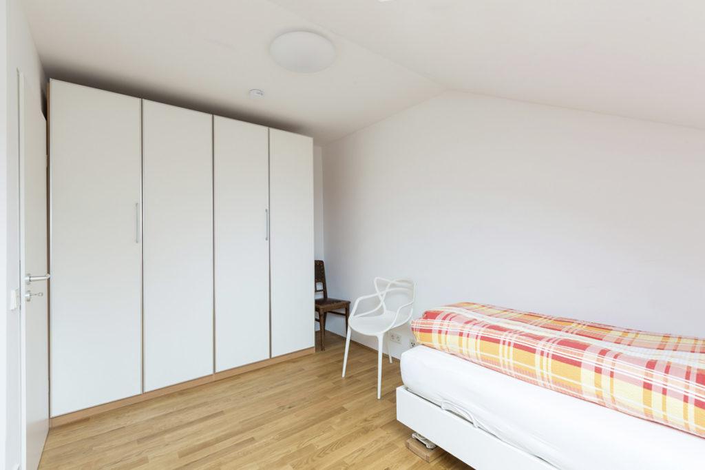 Schönes Schlafzimmer mit großem Schrank und Designer Stuhl