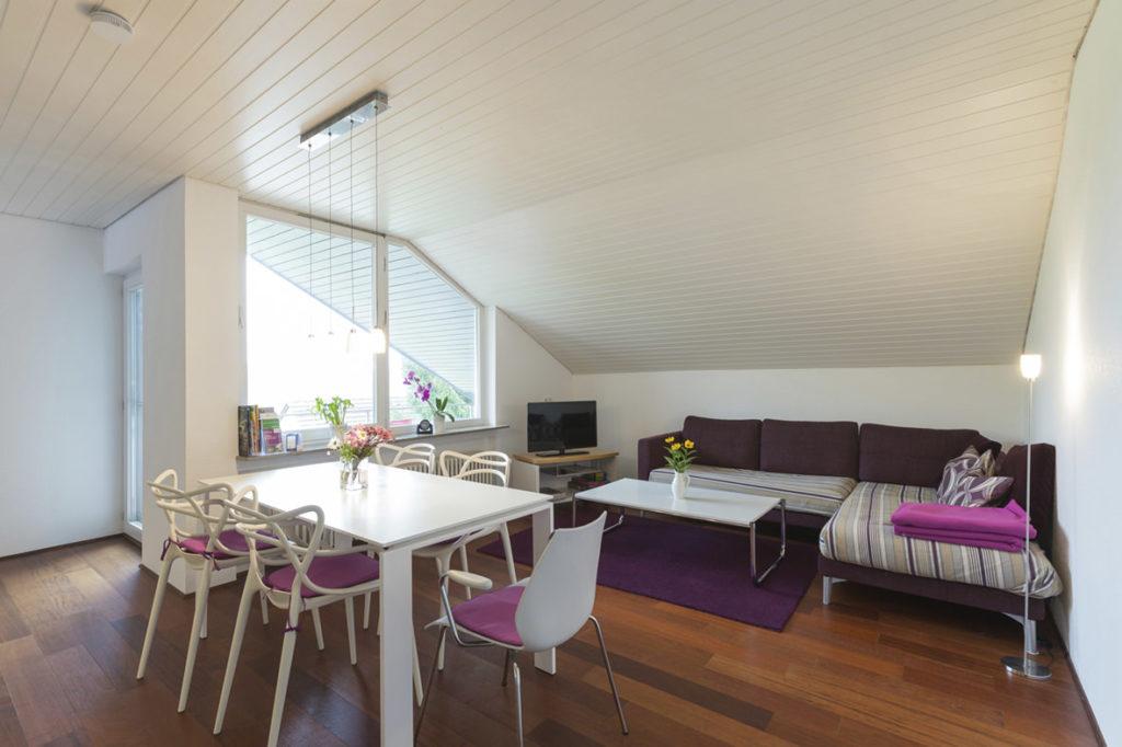 Großes gemütliches Wohn Esszimmer mit Sofaecke und großem Esstisch und Parkettfußboden